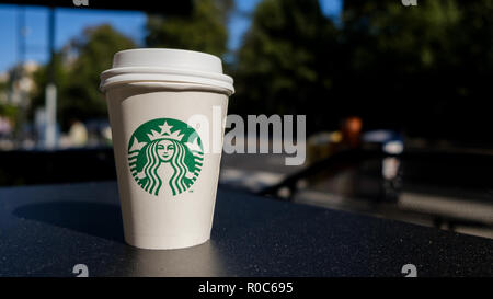 A cardboard, take out, Starbucks coffee cup on an outside table clearly showing the company twin-tailed mermaid branding logo. i - Stock Image