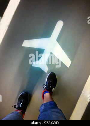 Anonymous person walking to an airport. Airplane sign painted on the floor parking of the airport - Stock Image