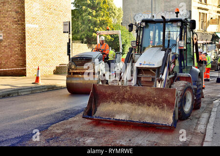 Road resurfacing digger loader and roller going over this and tarmac put down by surfacing machine - Stock Image