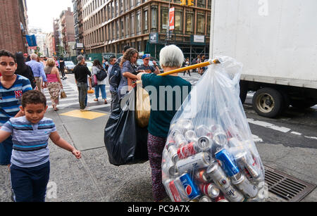 Old lady recollecting empty cans and bottles from street trash bins downtown Manhattan that she will exchange for recycling rewards - Stock Image