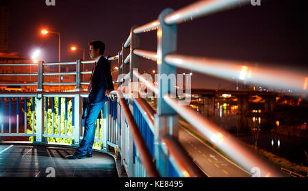 Businessman tired and gloomy in city at night - Stock Image