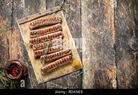 Grilled sausages with sauce. On a wooden background. - Stock Image