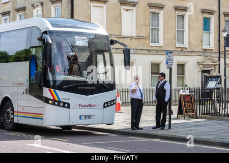 A pair of coach drivers chatting next to a parking sign and coach at the coach parking area North Parade in Bath - Stock Image