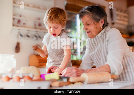 Happy senior great grandmother with small toddler boy making cakes at home. - Stock Image