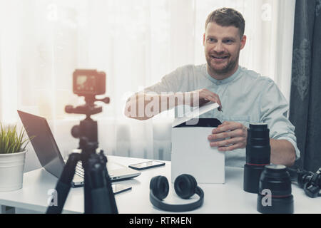 social media technology influencer recording unboxing video at home - Stock Image