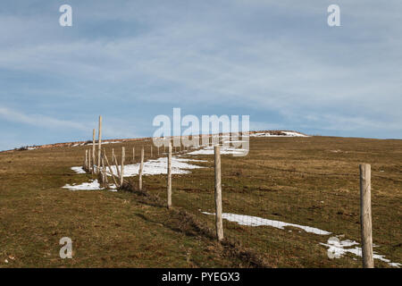 Wooden fence posts and barbed wire marking the property line of a prairie with dried grass and patches of snow under blue sky with white clouds - Stock Image