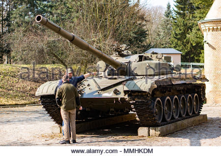 Two men standing by a old exhibition tank of a museum on the Cytadela park in Poznan, Poland - Stock Image