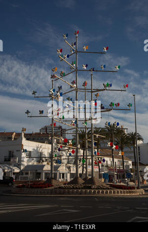Windmill sculpture on a  traffic island on the seafront, Benalmadena, Costa del Sol, Spain. - Stock Image