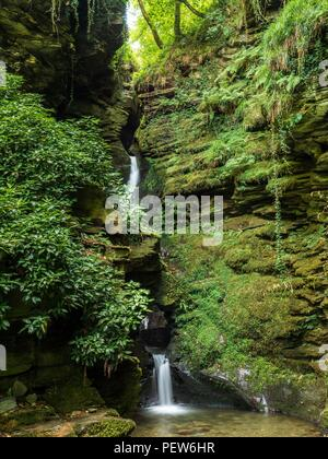 A waterfall running down a gully in the rock at St Nectan's Glen in Cornwall - Stock Image