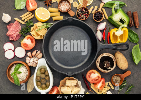 Italian food cooking ingredients on dark stone background with  cast iron pan flat lay and copy space. - Stock Image