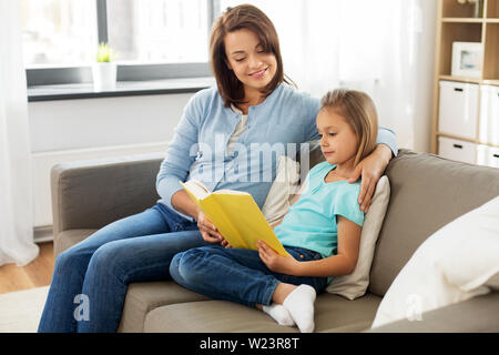 happy girl with mother reading book at home - Stock Image