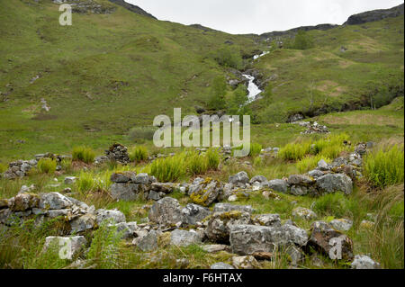 The remnants of an abandoned shiel in Glen Nevis with Allt Coire Giubhsachan tumbling from the Nevis range behind - Stock Image