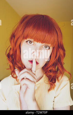 Young redhead woman doing a silent gesture - Stock Image
