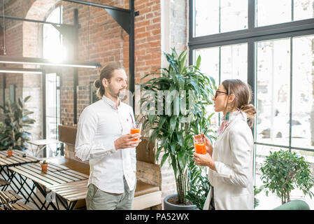 Young couple dressed in white standing together with drinks during the conversation in the beautiful loft interior - Stock Image