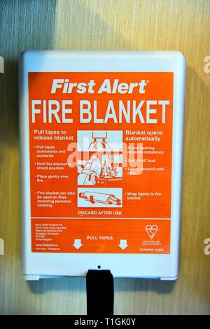 First Alert Fire Blanket attached to a caravan kitchen wall - Stock Image