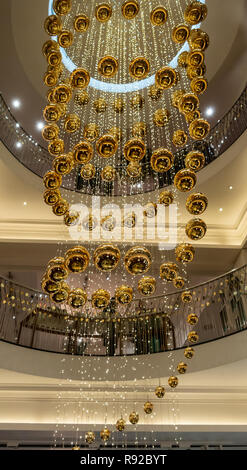 Cascade of shiny, reflective gold baubles in the stairwell of the historic Fortnum and Mason store in central London, England, UK - Stock Image
