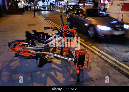 Mobike's left abandoned on pavement, Tottenham Court Road, London, England, UK - Stock Image
