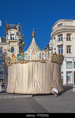 Charming old fashioned traditional carousel children's roundabout being closed up for the night in Place de l'Hotel de Ville St Quentin Aisne France - Stock Image
