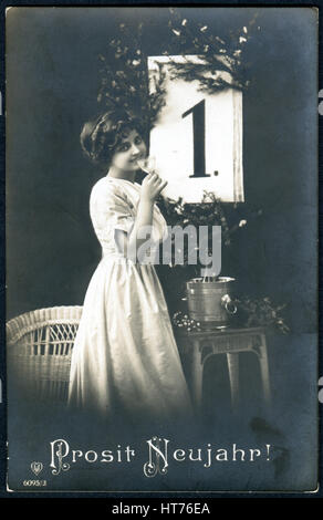 A greeting postcard printed in Germany, shows a woman with a glass of champagne. The inscription in German: Happy - Stock Image