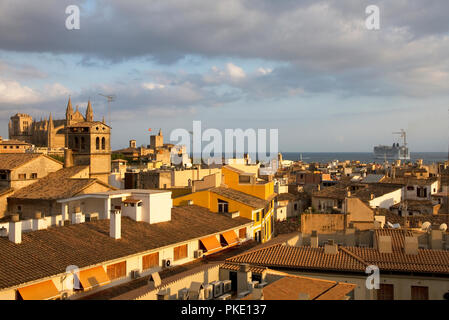 Palma, Majorca. City rooftops and cathedral in evening light with cruise liner leaving port. - Stock Image