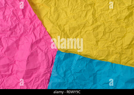 yellow, pink and blue crumpled paper texture as background. concept of school, abstract and stress - Stock Image