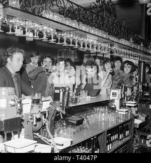 A group of mainly young men standing around  a bar in an English pub during the 1970s, mostly drinking beer. Black and white photograph. - Stock Image