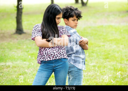 Brother and sister after an argument standing back to back with folded arms scowling outdoors in a garden - Stock Image