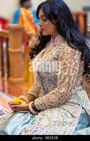 Profile of a very pretty Hindu woman holding a lotus flower at a service in South Richmond Hill, Queens, New York City. - Stock Image