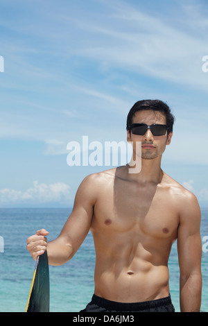 A man posing with a surfboard. - Stock Image