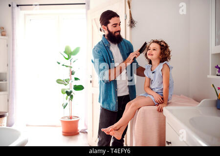 A young father brushing hair of happy small daughter in bathroom at home. - Stock Image