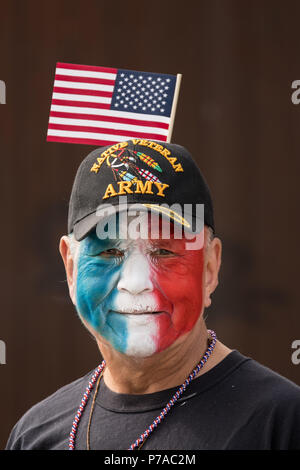 Anchorage, Alaska. 4th July, 2018. A Native American veteran wearing patriotic face paint and a flag hat during the annual Independence Day parade July 4, 2018 in Anchorage, Alaska. Credit: Planetpix/Alamy Live News - Stock Image