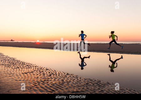 Female joggers at beach - Stock Image