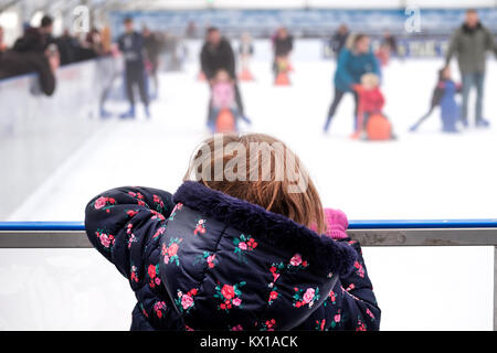 A young girl leaning over the barrier at an ice skating rink, watching other families on the ice with skating aids - Stock Image