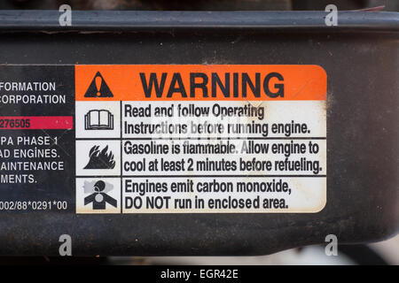 Warning signs or notices on a petrol engined lawnmower. - Stock Image
