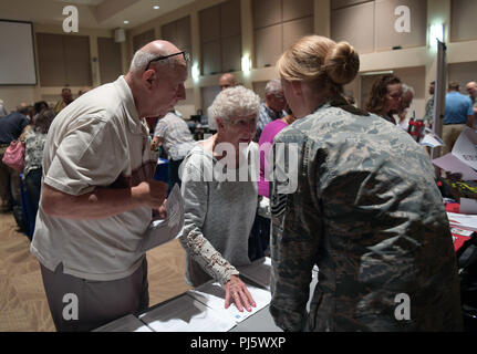 Master Sgt. Leah Calahan, far right, 460th Space Wing law office superintendent, speaks to attendees about legal services available to retirees during the Retiree Appreciation Day event at Buckley Air Force Base, Colorado, Aug. 25, 2018. In addition to representatives from the legal office, over 30 various support agencies were available to provide an in-depth explanation on services they can provide. The hope is for retirees in the local community to feel welcomed and content with reaching out to Team Buckley for any information they may need. (U.S. Air Force photo by Senior Airman Jazmin Smi - Stock Image