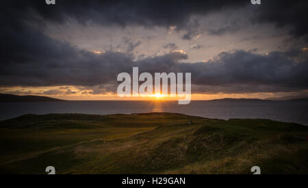 The sun setting over the horizon of the Atlantic Ocean behind Scarista Golf Course on the west coast of the Isle - Stock Image