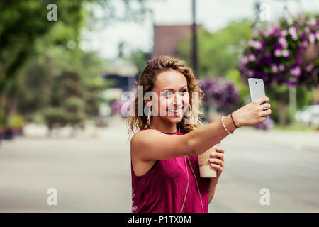 A young beautiful woman takes a self-portrait on a cell phone on a street near a university campus; Edmonton, Alberta, Canada - Stock Image