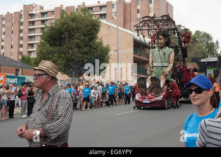 Jean-Luc Courcoult (braces & hat. Far bottom left of), walks ahead of his Little Girl Giant in Perth, Western - Stock Image
