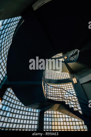 Beautiful and hypnotic spiral convoluted staircase with natural light coming through glass - Stock Image