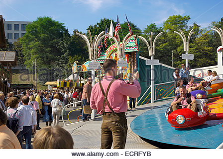 Man in Lederhosen uses cell phone to photograph people in amusement park ride, Oktoberfest, Germany. - Stock Image