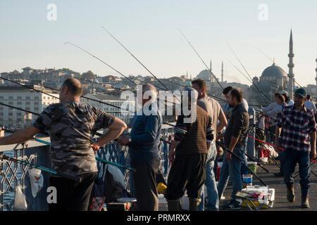 Recreational fishermen fishing from the Galata bridge over the Bosphorus in Istanbul, Turkey - Stock Image
