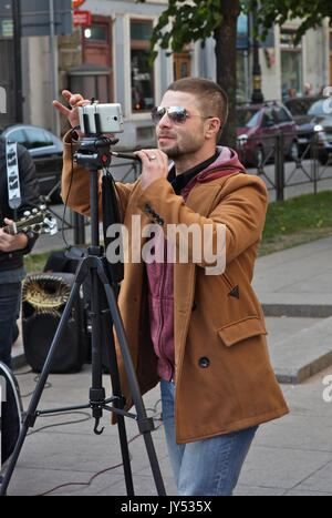 Man filming a street music group - Stock Image