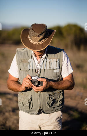 Man adjusting the lens of camera  during safari vacation - Stock Image