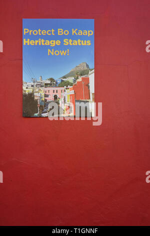 Sign to Protect Bo Kaap's heritage status campaign on a  typical red wall of the neighborhood in Cape Town, South Africa - Stock Image