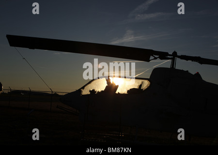 AH-1J SeaCobra helicopter silhouetted against the setting sun at the Carolinas Aviation Museum - Stock Image