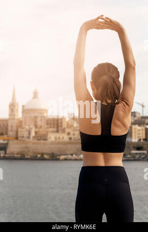 back view of a woman doing an arm stretch warm-up exercise. Valletta Malta background. - Stock Image