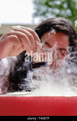 Female Student Demonstrates Quantum Magnetic Levitation and Suspension Effect. A splash of liquid nitrogen cools a ceramic superconductor forcing it t - Stock Image