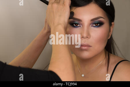 Makeup artist working with Asian model in beauty salon. Face sculpt. Contouring. Make up woman face. Contour and highlight. Beauty industry. Space for - Stock Image
