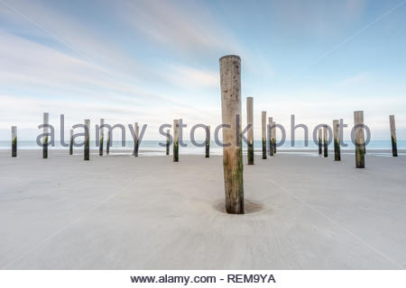 Poles on a beach with blue sky long exposure landscape - Stock Image