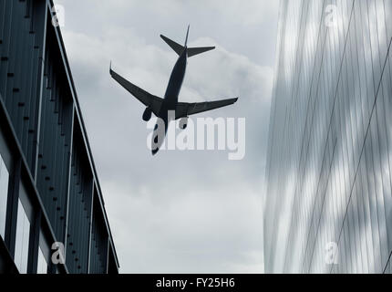 Passenger jet flying over buildings - Stock Image